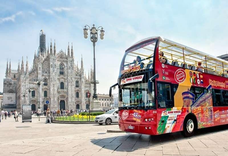 Ônibus turístico passando pela Catedral de Milão