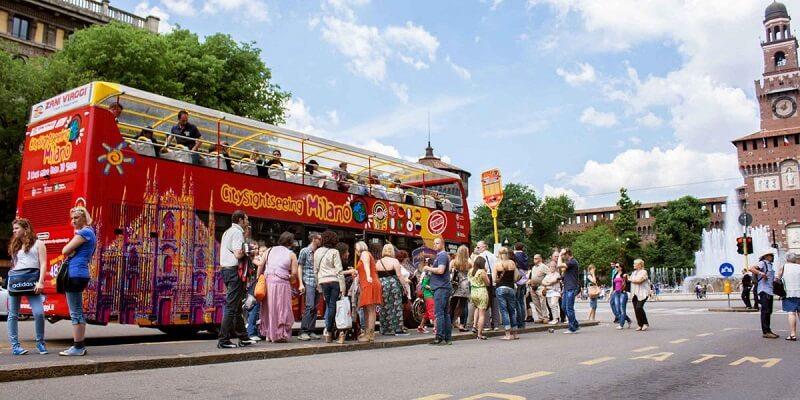 Turistas entrando no ônibus turístico