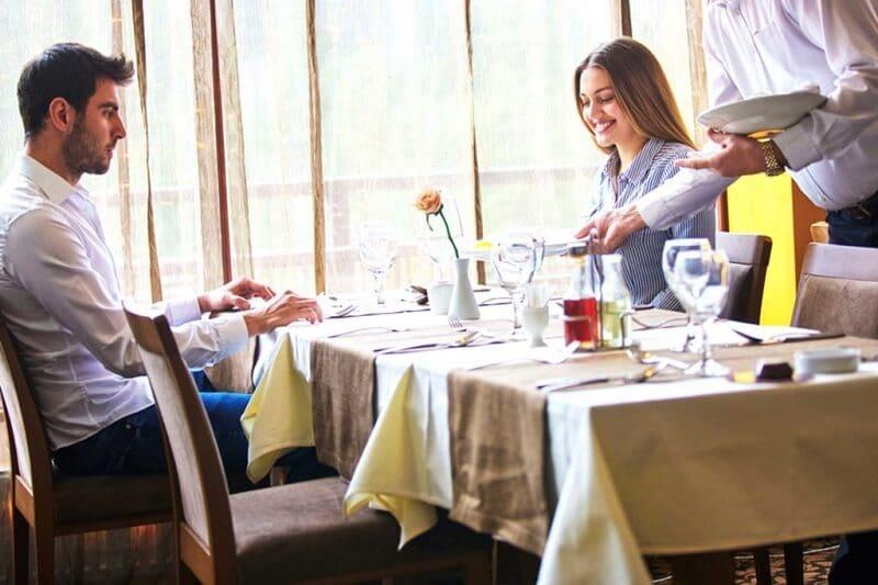 Homem e mulher sendo servidos em restaurante