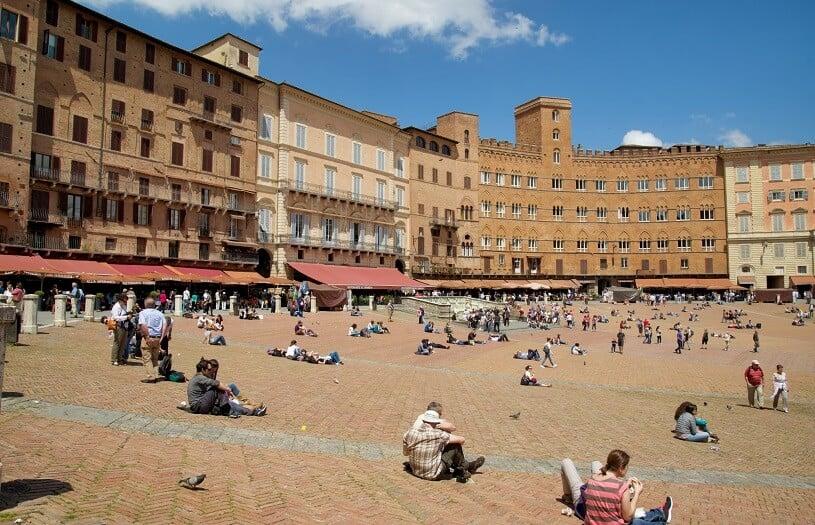 Pessoas sentadas na Piazza del Campo em Siena