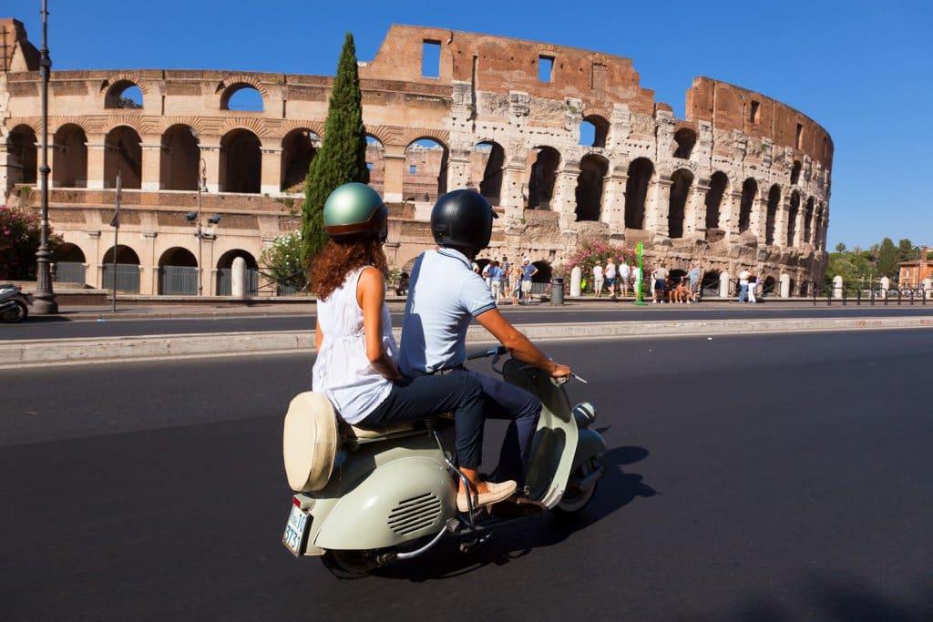 Pessoas andando de vespa em Roma