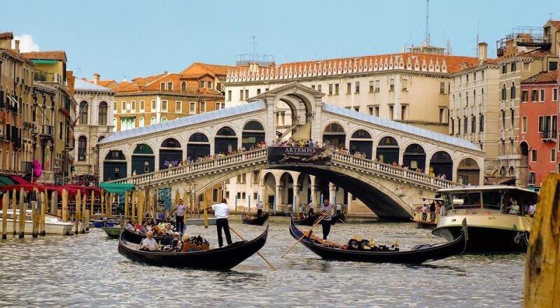 Pessoas fazendo passeio de gôndola em canal de Veneza