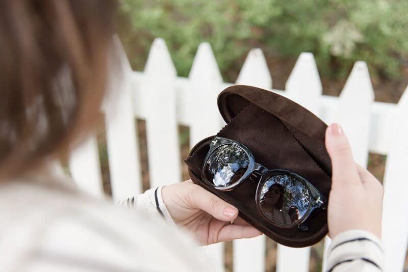 Pessoa segurando capa com óculos escuro