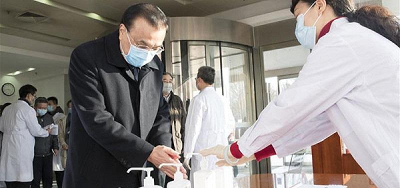 Pessoas com máscaras higienizando as mãos